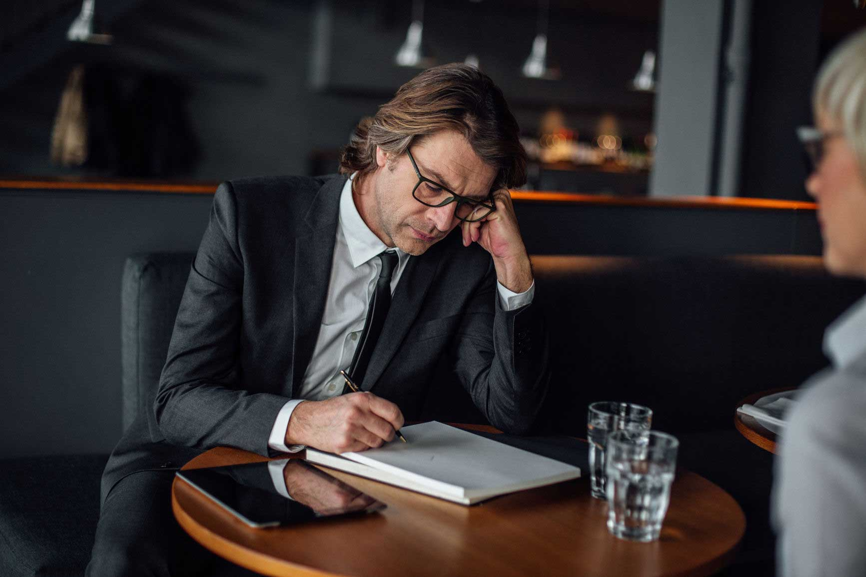 man sitting in a suit writing in a notebook